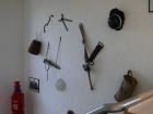 Eine Sammlung von historischen Gerätschaften der Feuerwehr Erbach an der Wand im Treppenaufgang zum 1. OG