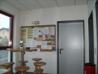 Das 1. OG mit 'schwarzem Brett', einem Stehtisch mit Stühlen für Besprechungen. Hier befinden sich auch die Zugangsmöglichkeiten zur Küche und den Schulungsrämen der Jugendfeuerwehr und der Einsatzabteilung