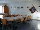 Der Schulungsraum der Einsatzabteilung mit Durchreiche zur Küche und Zugang zum Büro. Ein Beamer an der Decke, eine ausfahrbare Leinwand sowie einem Multimediaschrank ermöglichen modernen Theorieunterricht und helfen beim Vermitteln von Fachwissen