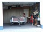 Die Garage. Hier finden sich eine historische und voll funktionstüchtige Handspritze sowie eine ebenfalls historische Pumpe. Auch Stauraum sowie die Abstellmöglichkeit für den Mehrzweckanhänger sind hier gegeben.