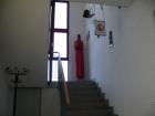 Treppenaufgang zum 1. OG, in dem sich Küche, Büro und die Schulungsräme für Jugendfeuerwehr und Einsatzabteilung befinden. Auf dem Podest der Treppe: ein restaurierter Feuermelder